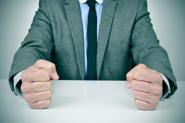 man in suit banging his fists on a desk