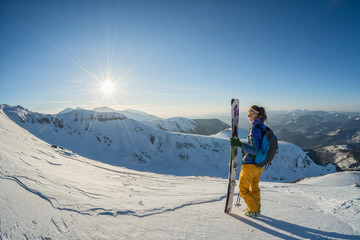 skier looking at the sunset from the top of the mountain