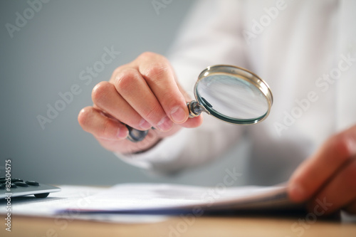 Businessman with magnifying glass reading documents - 82504575