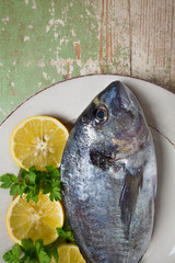 Fresh gilt-head bream with lemon and parsley served on a plate