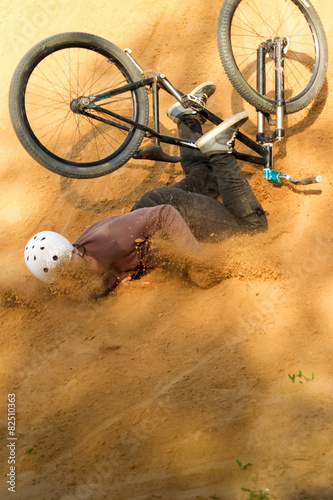 Deurstickers Fietsen biker is falling from his mountain bike to the sand