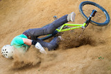 biker is falling from his mountain bike to the sand
