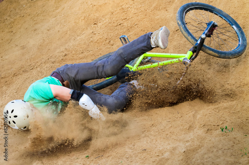 Staande foto Fietsen biker is falling from his mountain bike to the sand