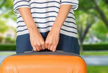 Woman. Woman in blue dress holds orange suitcase in hands on the