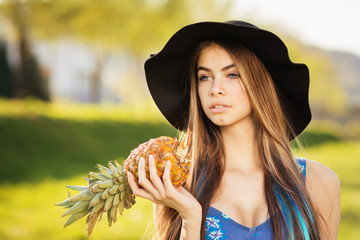 Gorgeous young blonde woman in fedora holding pineapple