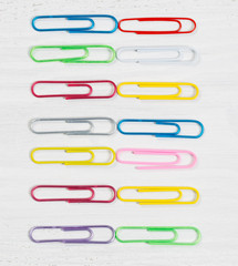 Colorful paper clips organized on white wood