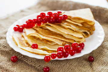pancakes and berries of currant in a plate