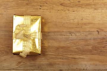 Goldenes Weihnachtsgeschenk auf Holz