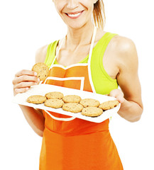 Baking woman showing cookies on tray