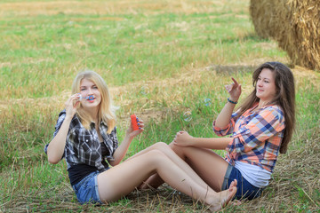Friends making iridescent soap bubbles on summer ranch