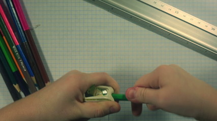 Child's hands sharpening a green pencil