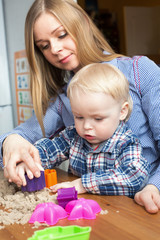 A cute little boy and wish mother playing with kinetic sand