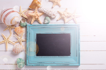Empty blackboard and marine items on wooden background.