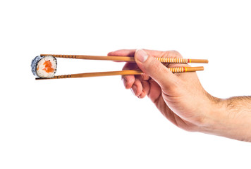 hand holding sushi with chopsticks