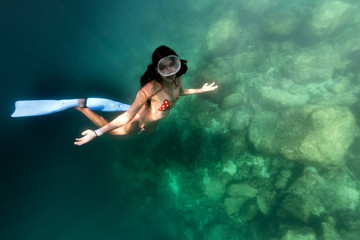 mexican beautiful girl swimming underwater looking at you