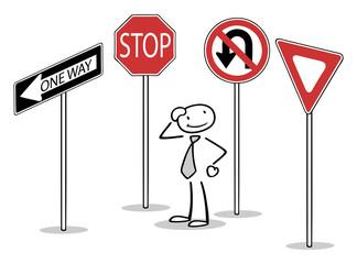 Mann steht zwischen vielen Verkehrszeichen