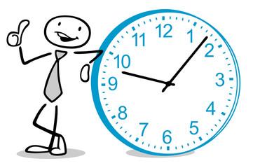 Mann lehnt an Uhr und hält Daumen hoch