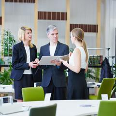 Geschäftsleute im Büro mit Akte reden