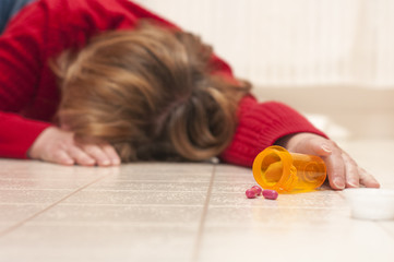 Unconscious woman on floor with open pill bottle