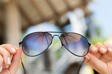 close up of hands holding shades or sunglasses