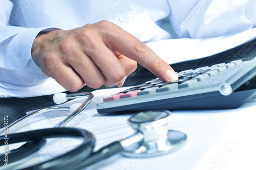 healthcare professional calculating on an electronic calculator плакат