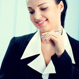 Smiling businesswoman with pen at office
