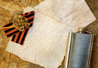 Paper flowers,Saint George ribbon,hip flask on a sackcloth