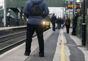 Man standing on station platform as train pulls in