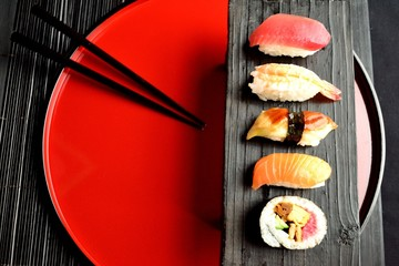 Mixed sushi platter with chopsticks on red tray
