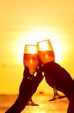Man and woman clanging wine glasses with champagne at sunset poster
