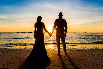 The bride and groom are kept hands on a tropical beach .