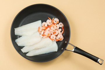 A pan with raw seafood, white fish and shrimps