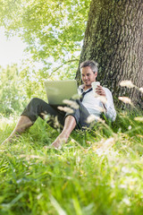 handsome grey hair man using a laptop, barefoot in the grass