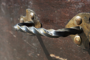 iron hammered handle attached to a wooden surface