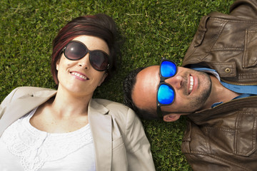 Sunglasses couple posing at city park grass