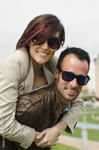 Young couple with sunglasses smiling at city park Poster