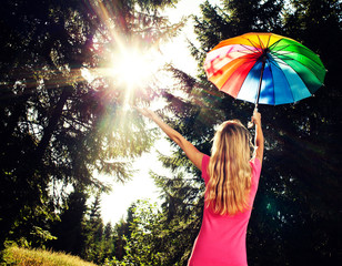 Woman with umbrella standing in the forest and looking at sun