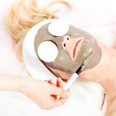 Beauty skin treatment, beautician applying clay mask
