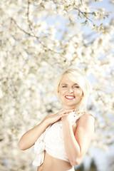 Hübsche blonde Frau vor blühendem Frühlings Baum