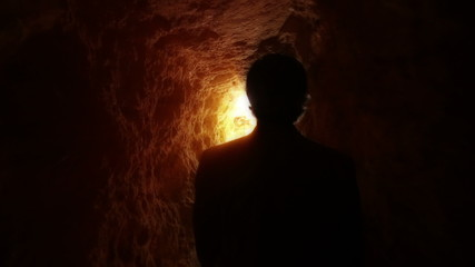 Man exits from dark cave to light in exterior, slow motion