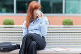 Businesswoman is sitting outside on a metal bench and drinking c