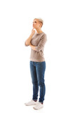 Casual dressed woman is standing and thinking over white isolate