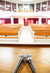 Closeup microphone in empty church with empty pews