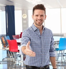 Casual businessman offering hand in meeting room