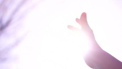 Sun's rays through fingers of female hand