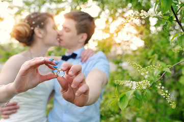 Bride and groom holding rings and kiss