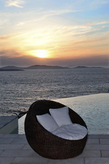 Rattan pool chair at sunset