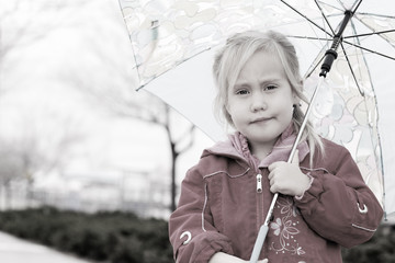 adorable blonde girl holding colorful umbrella walking in the st