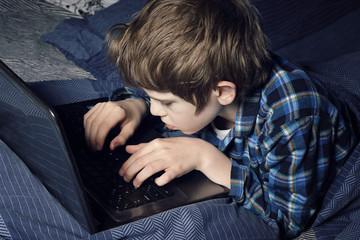 enfant garçon au lit avec ordinateur portable