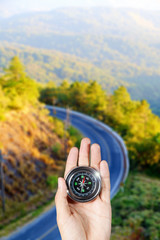 The hand of a man holding a compass over a landscape road view